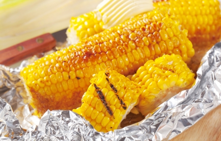 Pieces of sweet corn grilled in tin foil photo