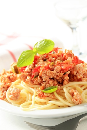 Minced meat sauce served on a bed of cooked spaghetti photo