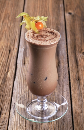 Glass of chocolate smoothie garnished with fresh fruit photo