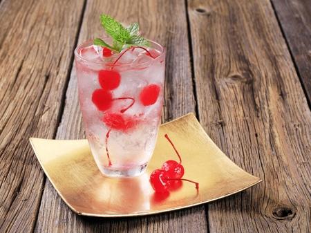 maraschino: Glass of iced drink with maraschino cherries
