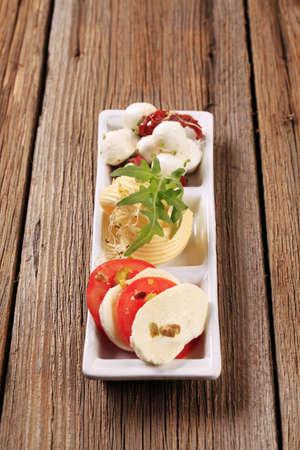 Mozzarella cheese, fresh tomato and butter - closeup photo