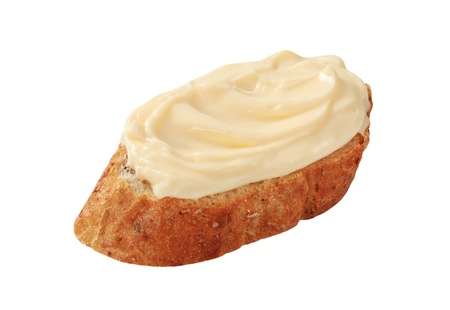 Slice of bread roll and creamy cheese spread photo