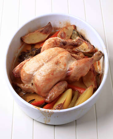 Chicken with potatoes , carrot and celery baked in a casserole dish photo