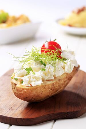 Baked potato topped with cheese - closeup photo