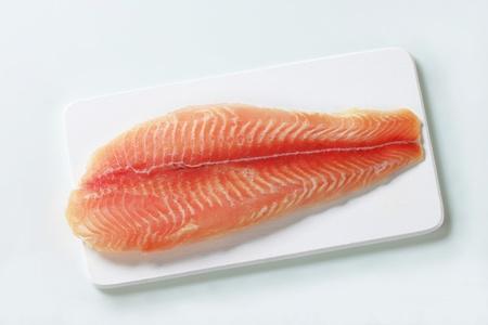 alaska pollock: Raw fish fillet on cutting board