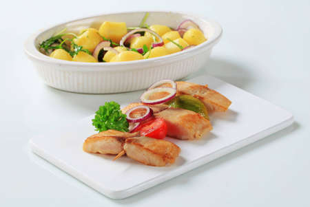 Fish skewer and potatoes in casserole dish Stock Photo - 12444041