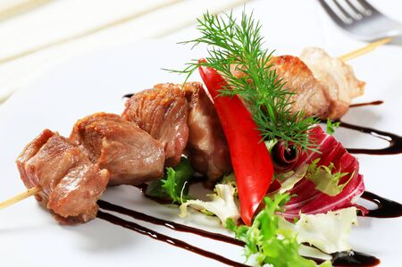 balsamic: Pork skewer garnished with fresh salad and balsamic vinegar