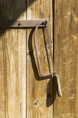 serrucho: Serrucho oxidado que cuelga en la puerta de madera Foto de archivo