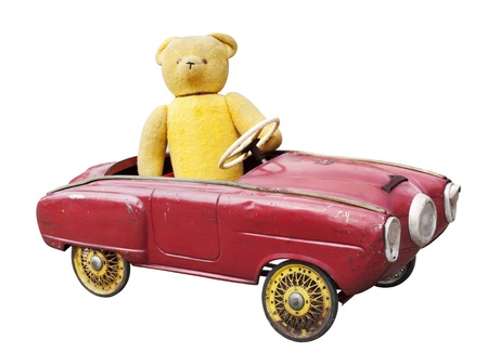 plush toy: Old teddy bear in a vintage toy car isolated on white Stock Photo