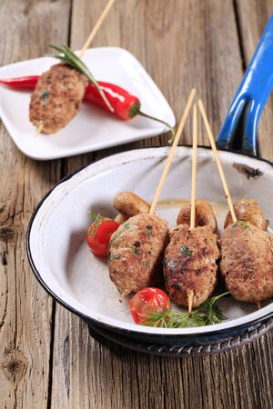 Minced meat kebabs on wooden skewers and mushrooms photo