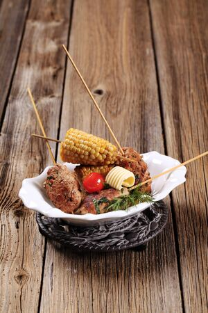 Minced meat kebabs on wooden skewers and roasted sweetcorn photo