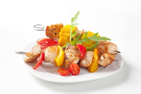 Grilled meat and vegetable on skewers and ketchup photo
