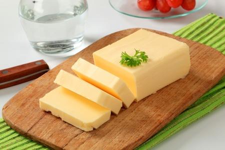 mantequilla: Bloque de la mantequilla fresca en una tabla de cortar Foto de archivo