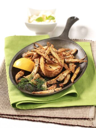 Fried anchovies and potato on cast iron pan photo
