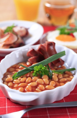 bacon baked beans: English breakfast of baked beans, sausages, fried egg and bacon
