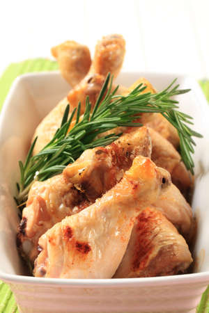 Chicken drumsticks with rosemary in a casserole dish photo