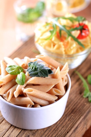penne: Bowl of whole wheat pasta tubes - closeup