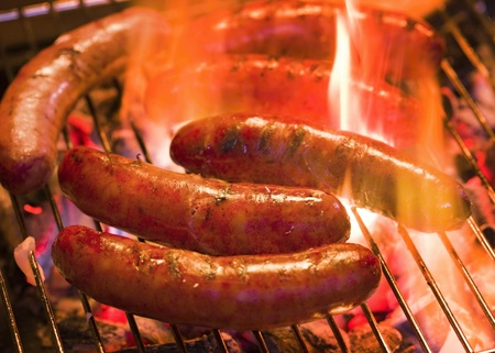 Grilling bratwursts on a charcoal grill Stock Photo