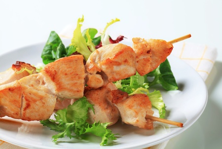 Chicken skewers and mixed salad greens photo
