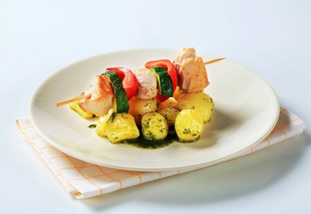 Chicken skewer with potatoes and pesto sauce photo
