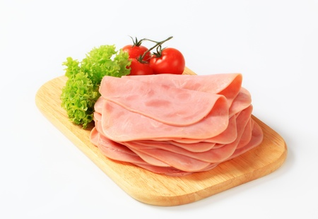 thinly: Thinly sliced ham on a cutting board Stock Photo