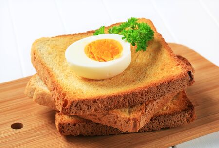 Slices of toasted bread and boiled egg photo