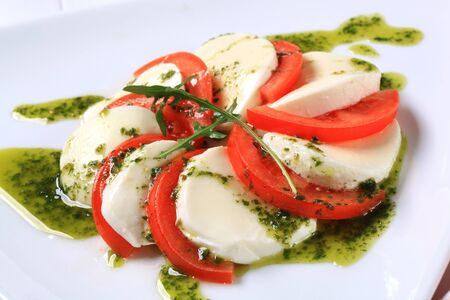Slices of mozzarella cheese and tomato seasoned with pesto sauce photo