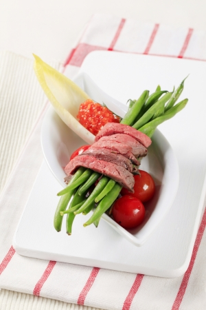 Strips of roast beef and fresh vegetables photo