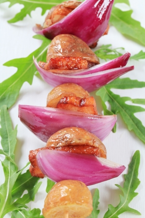 Pork and bacon skewers with potatoes and Spanish onion photo