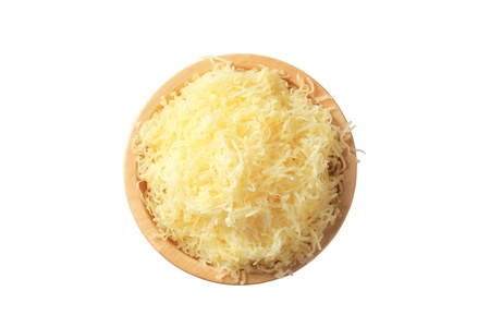 shredded cheese: Grated cheese in a wooden bowl