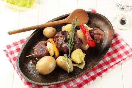shish kebab: Beef shish kebab and new potatoes on cast iron plate