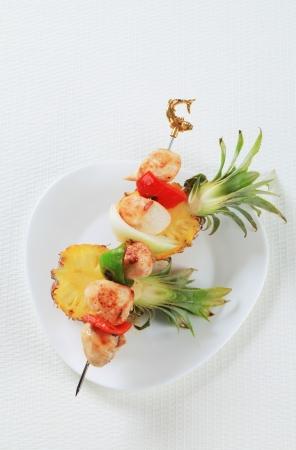 Chicken skewer on fresh pineapple photo