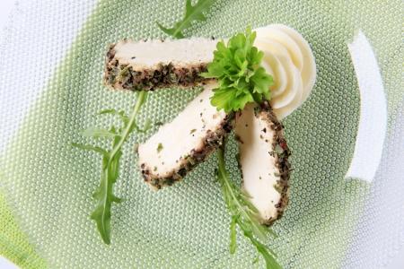 queso de cabra: Rebanadas de queso de cabra recubierto de hierba - Detalle Foto de archivo