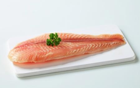 Raw fish fillet on cutting board photo