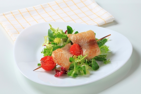 alaska pollock: Fish skewer on a nest of salad greens