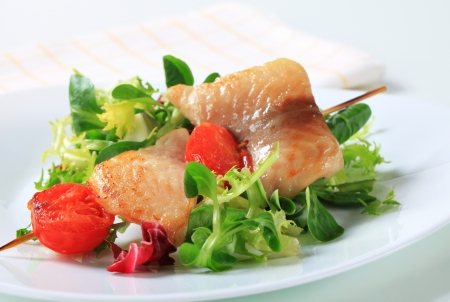 Fish skewer on a nest of salad greens Stock Photo - 14548501