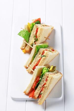 bocadillo: Tri�ngulos s�ndwich vegetales en la tabla de cortar Foto de archivo