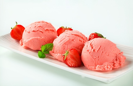 Scoops of strawberry ice cream and fresh strawberries photo