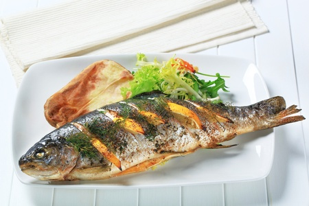 Oven baked trout stuffed with lemon and dill photo