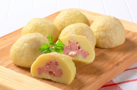 Meat stuffed potato dumplings on cutting board photo