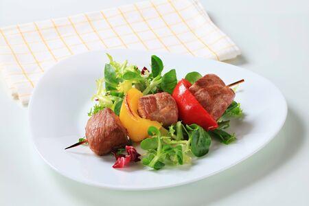 greens: Grilled pork skewer with fresh salad greens