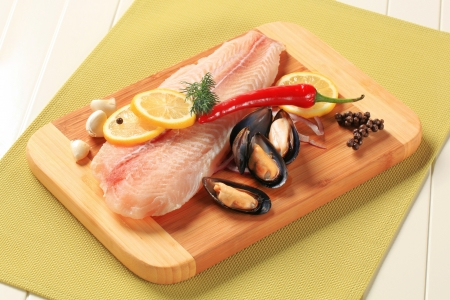 Fresh fish fillet and mussels on a cutting board photo