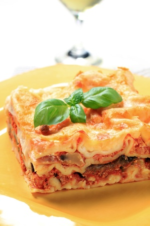 Portion of lasagna on a yellow plate photo