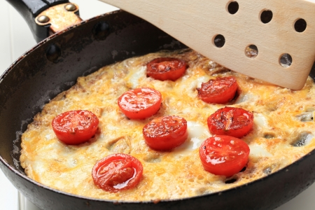 Egg omelet and cherry tomatoes in a frying pan photo