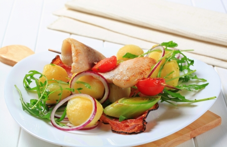 Fish skewer and potatoes with leek and arugula photo