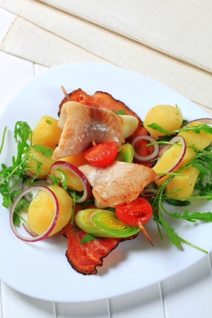 Fish skewer and potatoes with leek and arugula Stock Photo - 15608755