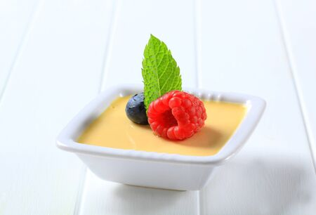 vanilla pudding: Small dish of vanilla custard topped with fruit