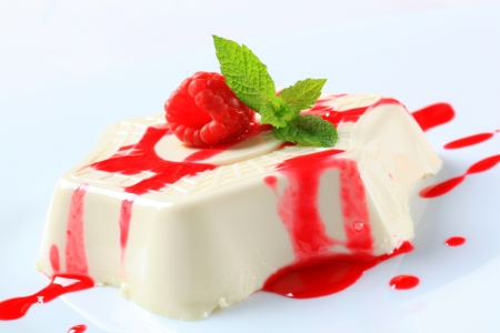 Panna cotta with fruit coulis and raspberry photo