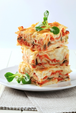 Three portions of lasagne stacked on a plate photo