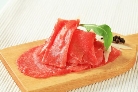 thinly: Thinly sliced raw beef meat on cutting board